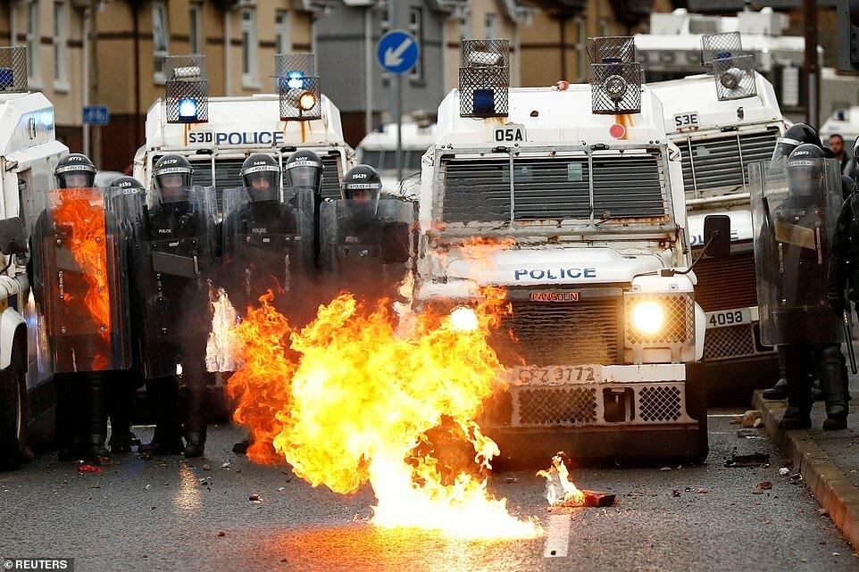 Перед полицейскими машинами в Белфасте горит пожар. В городе продолжаются акции протеста между офицерами и молодежью.