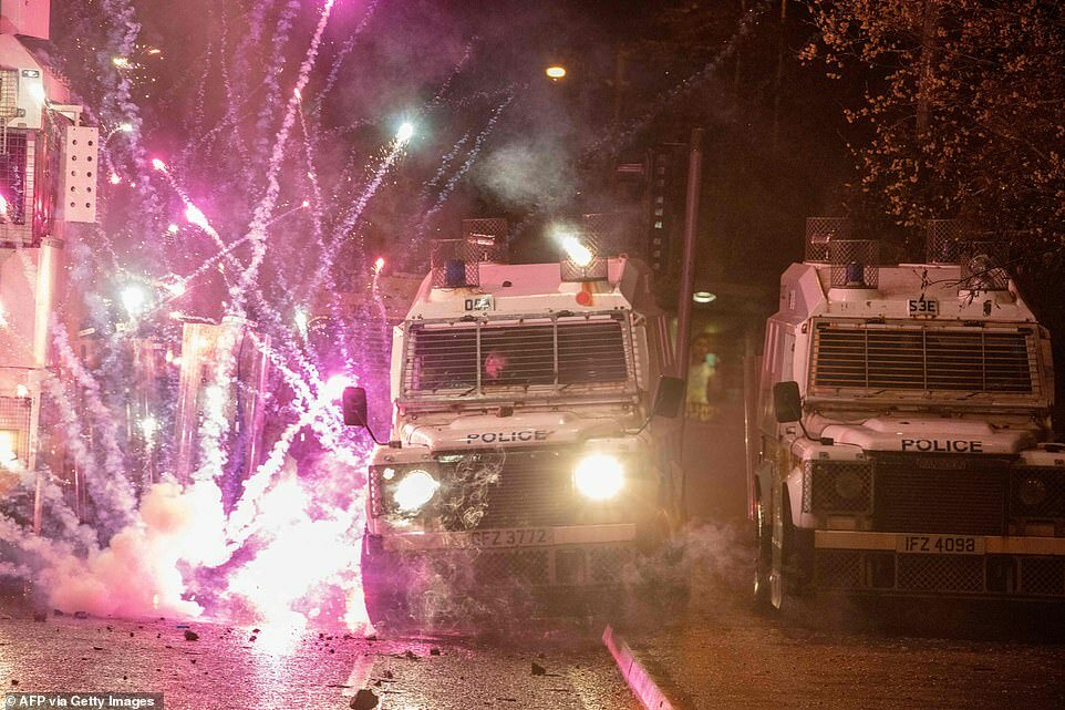 Фейерверк взрывается на полицейских машинах после обстрела полицейских во время столкновений с националистической молодежью на Спрингфилд-роуд