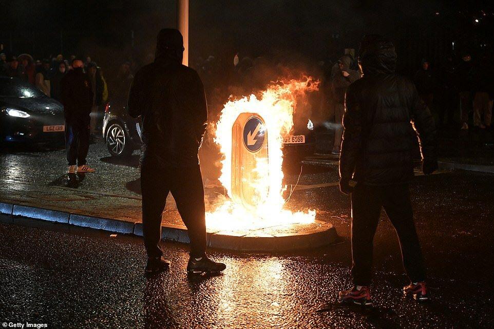 Люди смотрят, как горит дорожный знак, когда националисты нападают на полицию на Спрингфилд-роуд возле Стены мира