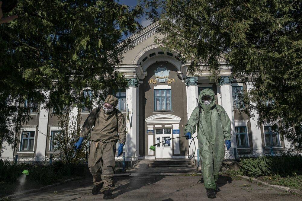 Пожежні в захисних костюмах розпорошують хлор перед лікарнею в Почаєві