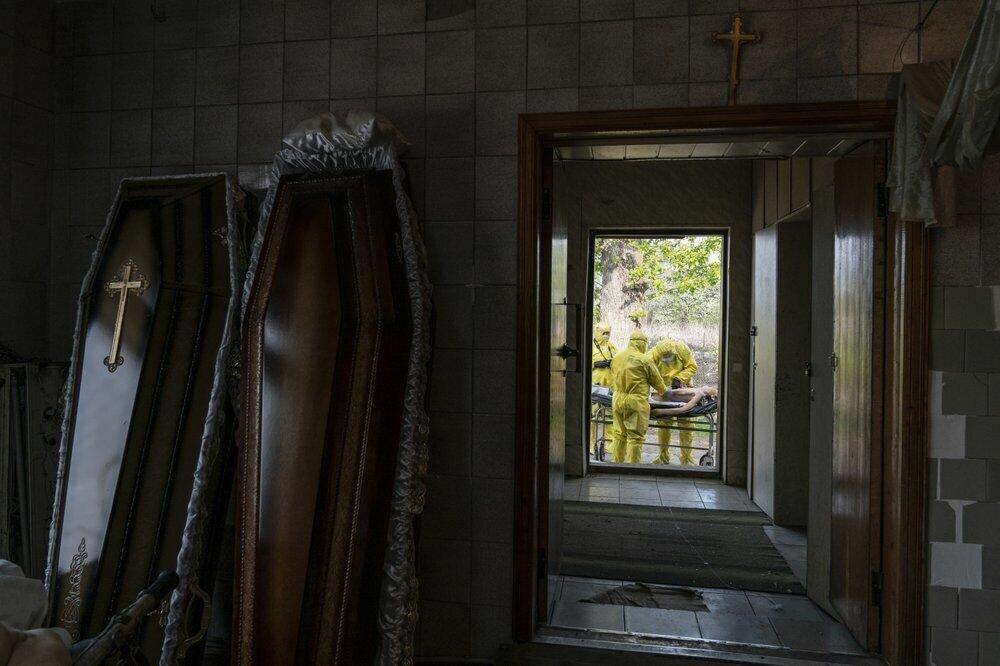 Патологоанатоми в спеціальних костюмах біля тіла людини, яка померла від коронавируса, під моргом однієї з лікарень в Тернополі