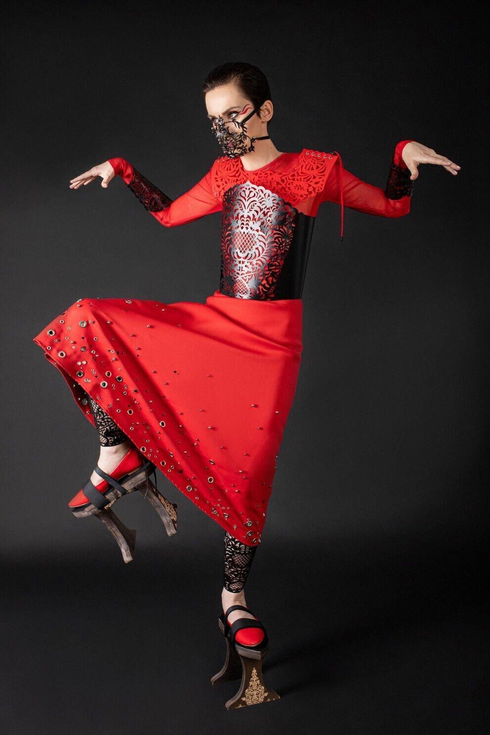 Павленко примерила длинное красное платье с украшениями на юбке, черным ажурным корсетом и маску