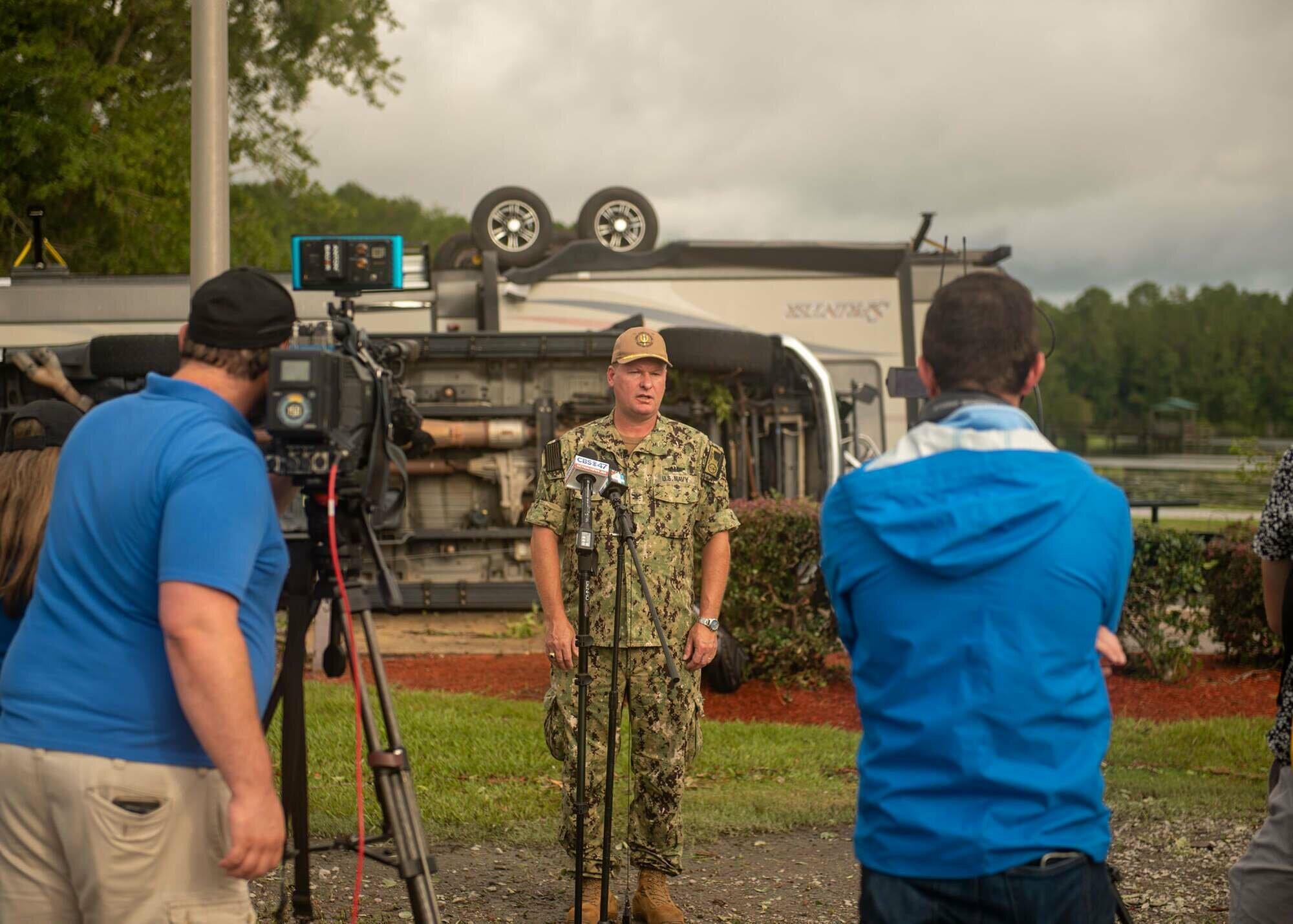 Военный дает комментарий на фоне перевернутого фургона